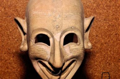 maschera in ceramica raffigurante volto umano, con espressione ghignante, decorata con motivi impressi di rosette, sole, serpenti e palme sulla fronte e sul mento, linee incise sulle gote che rievocano i tatuaggi, fori nelle orecchie e nel naso dove è presente un anellino argenteo